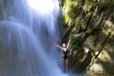 Woman with black bikini  hapy under waterfall at Erawan Waterfall and  natural in Kanchanaburi province, Thailand