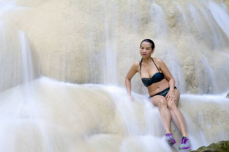 Woman pretty and bikini sit on waterfall at Erawan Waterfall and  natural in Kanchanaburi province, Thailand