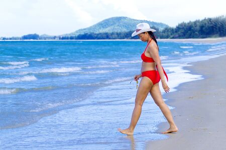 Woman with red bikini walk on beach at Ban Krut Beach, in Prachuap Kirikhun Province Thailand is famous for travel