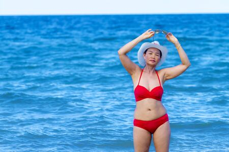 Woman with red bikini shape sexy on beach at Ban Krut Beach, in Prachuap Kirikhun Province Thailand is famous for travel