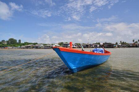 Petit bateau de pêche et le village au bord de la mer à Rayong, en Thaïlande.