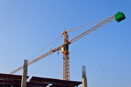 cranes at construction site against blue sky photo