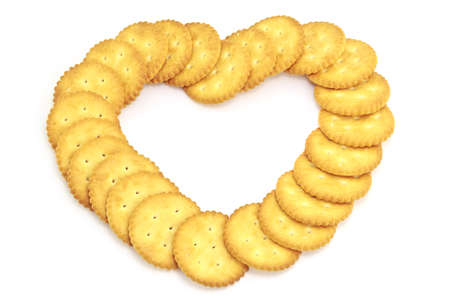 Biscuit arranged in a heart shape on white background photo