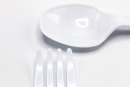 Cost-up plastic spoon and fork isolated on white background. It copy space and selection focus.