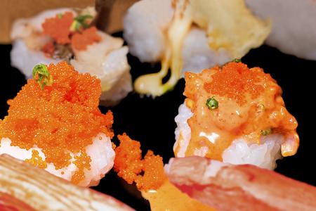 Sushi set sashimi and sushi rolls served on black stone slate. Close Up.