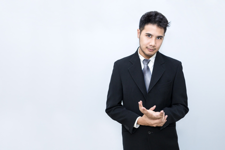 Young handsome businessman smiling and smart at office.He is 20-30 years old in black suit.Copy space.