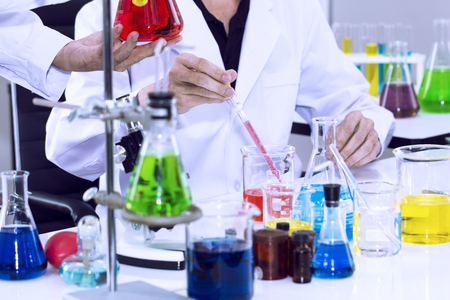 Senior handsome researcher mixing with color test tube.Doctor in white suit and glasses.Copy space. Archivio Fotografico