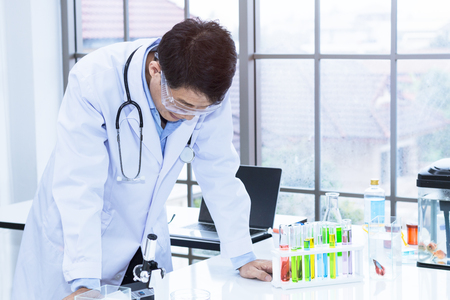 Senior handsome researcher working overtime and strain near laboratory instrumentsat hospital.Doctor in white suit and glasses.Copy space. Banque d'images