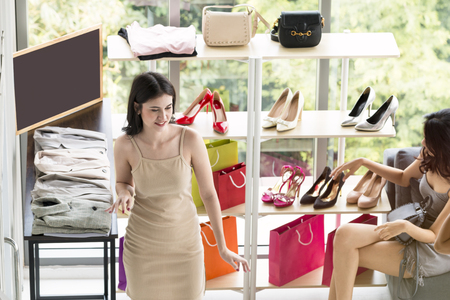 Young beautiful woman and friendship enjoying in shopping at shop.Lady choosing shoes and accessories . Copy space and top view.