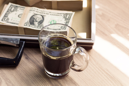 Fresh homemade black coffee and dollar in breakfast.Copy space.