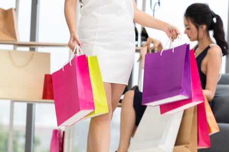 Young beautiful woman and friend with shopping bags enjoying in shopping at clothing store.Lady choosing bags. Copy space.