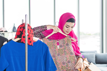Young beautiful woman with shopping bags enjoying in shopping at clothing store.Lady in hijab choosing clothes. Copy space.