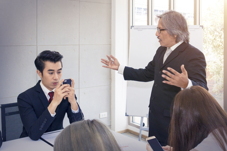 Young businessman is secretly playing on the smartphone at work.Senior manager angry and strain present project with team .Copy space. Imagens