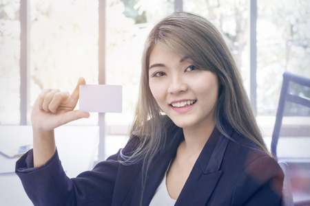 Young businesswoman smiling and thinking about project work at office.Lady holding credit card.Copy space.