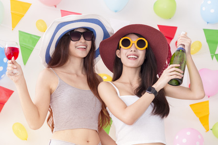 Young beautiful women celebrate holiday party and dancing.Best friends wearing casual shorts and T-shirt,having fun,drinking alcohol cocktails.Pastel tone.