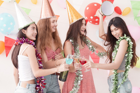 Young beautiful women celebrate holiday party and dancing.Friendship wearing dress,casual shorts and T-shirt,having fun,drink champagne and alcohol cocktails in holiday.Pastel tone.