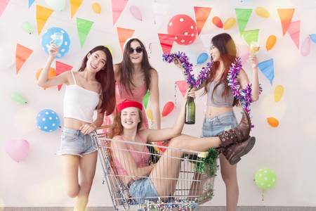 Young beautiful girl sitting in shopping cart in celebrate holiday party and friendship dancing.Friend group wearing dress,casual shorts and T-shirt,having fun,drink champagne and alcohol cocktails.