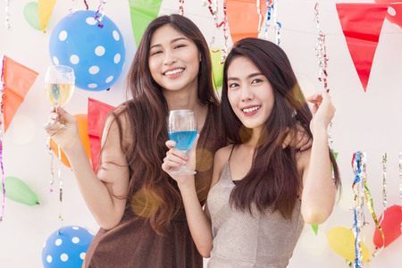 Young beautiful women celebrate holiday party and dancing on white wall.Best friends wearing dress posing ,having fun,drinking alcohol cocktails and champagne.Pastel tone.