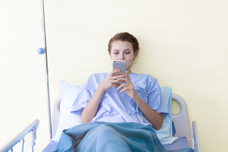 Attractive young woman patient working and typing information on mobile phone in  hospital bed. Connected world to business project when sick.Copy space. Imagens
