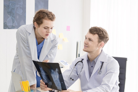 Medical professionals caucasian man holding xray and conversation about patient with young doctor woman in room hospital and clinic.Cheerful doctor gives good news. Close up and copy space.