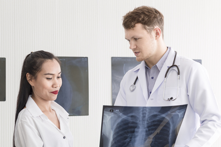 Medical professionals caucasian man holding xray and conversation with young woman Asia patient.Close up and copy space.