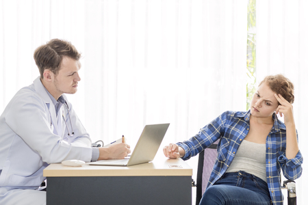 Medical professionals caucasian man reassuring and talking with young woman stress patient.Close up and copy space.