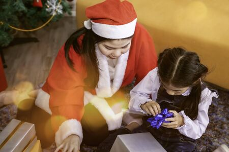 Joyful little girl and mother holding Christmas gifts boxes. Archivio Fotografico