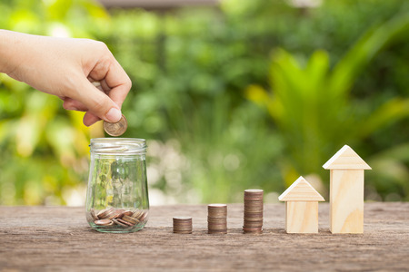 Hand's women putting golden coins in money jar. Concept of real estate investments, Home insurance, Savings plans for housing. , The concept of financial savings to buy a house. 스톡 콘텐츠