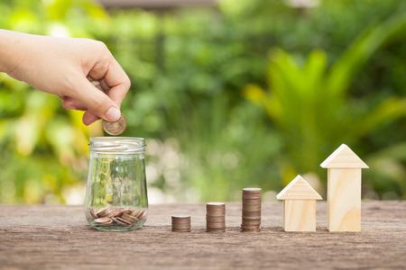 Ręka kobiety stawia złote monety w pieniądze słoju. Koncepcja inwestycji w nieruchomości, ubezpieczenie domu, plany oszczędnościowe na mieszkania. , Pojęcie oszczędności finansowych na zakup domu.