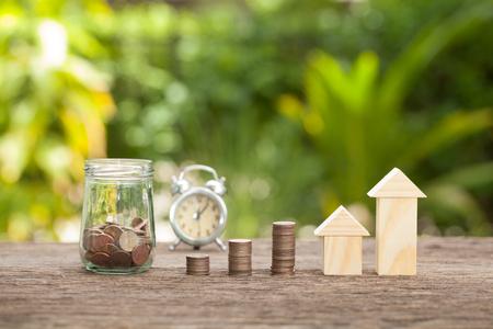 金瓶の中のコインを保存する時間。不動産投資は、ホーム保険、住宅貯蓄プランのコンセプトです。、家を購入する金融貯蓄の概念。