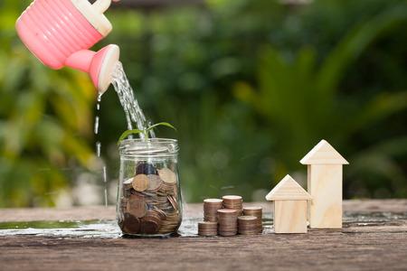 Geld en plant met gieter en geldboom, Geld besparen concept, concept van de financiële besparingen om een ??huis te kopen, bomen groeien in een reeks van kieming op palen van munten, groei, het bedrijfsleven, geld.