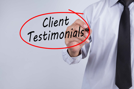 Businessman Hand Writing Client Testimonials with a marker over transparent board,  Business concept. Stock Photo