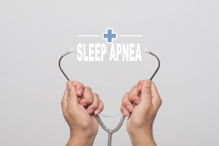 somnambulism: Hands holding a stethoscope and word  SLEEP APNEA on gray background. concept Healthy.