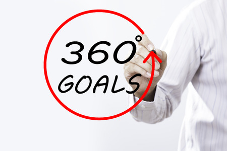 Businessman hand writing 360 degrees goals  with marker on transparent board. Business, internet, technology concept.