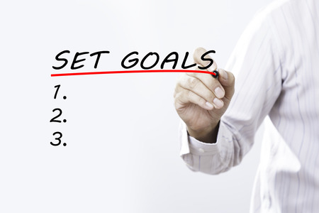 Businessman hand writing set goals with red marker on transparent wipe board, business concept
