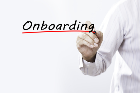 Businessman hand writing onboarding with red marker on transparent wipe board, business concept