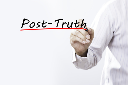 deceptive: Businessman hand writing post-truth with red marker on transparent wipe board, business concept Stock Photo