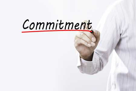 Businessman hand writing commitment with red marker on transparent wipe board, business concept.