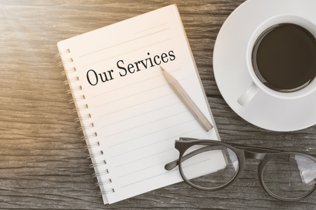 Concept Our Services message on notebook with glasses, pencil and coffee cup on wooden table. Banque d'images