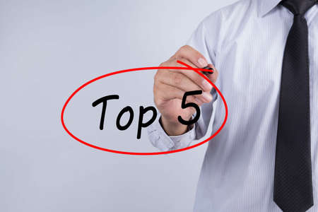 Businessman writing Top 5 with marker on transparent board. Business, internet, technology concept.