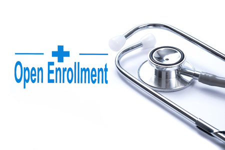 Page with Open Enrollment on the table with stethoscope, medical concept.
