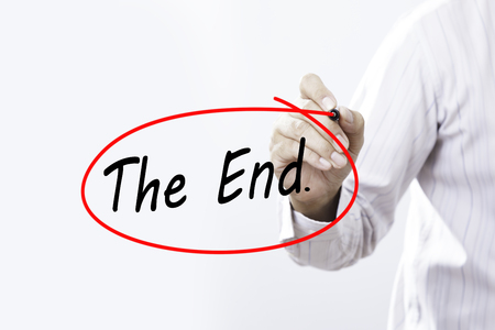 conclusive: Businessman Hand Writing The end. with a marker over transparent board,  Business concept. Stock Photo