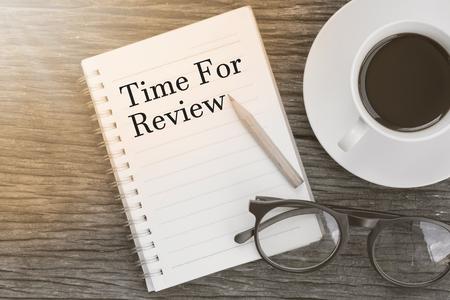 木製のテーブルにメガネ、鉛筆、コーヒー カップのノートブックの概念レビュー用に時間のメッセージ。