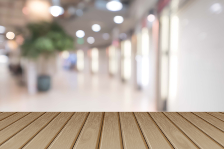 interior desing: Empty wooden table over blurred shopping mall background, for product display montage. Stock Photo