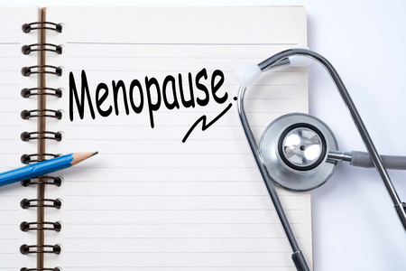 Stethoscope on notebook and pencil with menopause words as medical concept Stock Photo