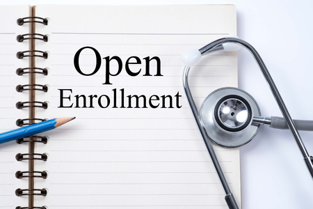 Stethoscope on notebook and pencil with Open Enrollment words as medical concept. Stockfoto