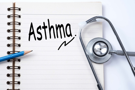 Stethoscope on notebook and pencil with Asthma words as medical concept