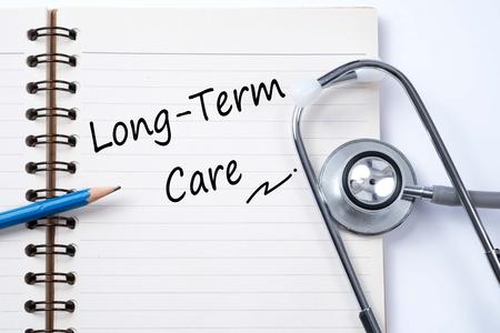 ノートと鉛筆ロングタームケアー言葉医療概念としての聴診器 写真素材