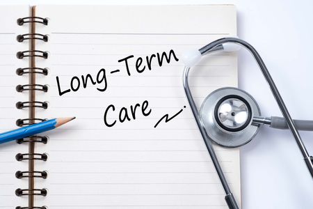 Stethoscope on notebook and pencil with Long Term Care words as medical concept