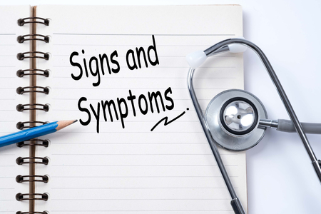 Stethoscope on notebook and pencil with signs and symptoms words as medical concept Stock Photo